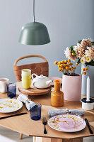 Gedeckter Tisch mit Teekanne, Vasen und Blumen
