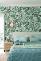 Double bed with blue and green covers in bedroom with botanical wallpaper