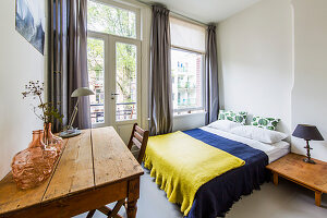 Vase on wooden table and double bed in bedroom