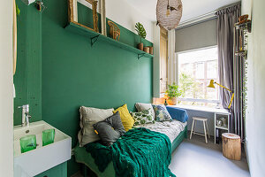 Scatter cushions on bed and sink in room with green accent wall
