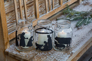 White candles in mason jars painted with festive silhouettes