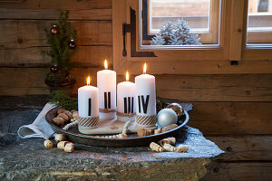 Advent arrangement of candles painted with Roman numerals on tray