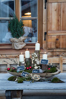 Advent arrangement of white candles on logs with numbered signs