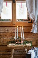 Vier Stabkerzen im Kerzenhalter aus Kupferrohren als Adventskalender