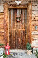 Laterne, Konifere und Kranz an rustikaler Haustür im Holzhaus