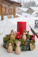 Rote Kerzen im Tablett mit Moos und kleinen Holzengeln im Schnee