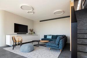 Blaues Ecksofa und langes Sideboard im modernen Wohnzimmer