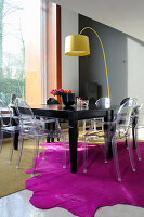 Transparent designer chairs around black table on hot-pink fur rug