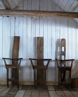 Three chairs made from reclaimed wood against board wall in wooden house