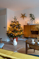 Illuminated Christmas tree in living room decorated in mid-century modern style