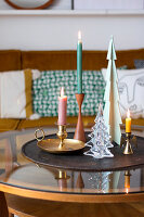 Colourful candles in different candle holders and Christmas-tree decorations