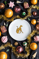 Plate with leopard motif on black fabric surrounded by Christmas-tree baubles