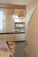 Open-plan kitchen with dining table and fitted plywood furnishings
