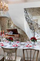 Festlich gedeckter Tisch in Rot und Weiß im eleganten Landhaus