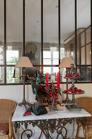 Sculpture, knick-knacks and Christmas decorations on table below interior window