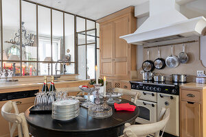 Set, round table in elegant country-house kitchen with interior window