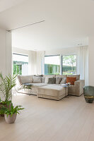 Pale grey modern sofa in bright open-plan living room