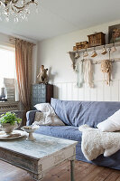 A sofa with a blue cover and a sheepskin in a shabby-chic style living room