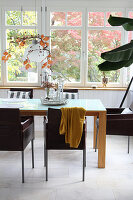 Dark chairs at wooden table in dining room in conservatory