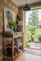 Rustikaler Konsolentisch mit Bild vor Tapete