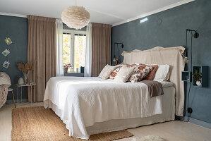 Doppelbett mit Bettwäsche und Tagesdecke in Beige, vor grauer Wand