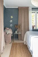 Beistelltisch vor beigefarbenem Vorhang im Schlafzimmer mit grauer Wand