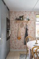Einbauküche mit grauen Fronten, runder Esstisch und rosa gemusterte Tapete an der Wand
