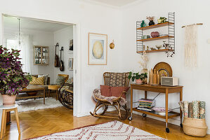 Rocking chair and serving trolley next to open doorway in bright room