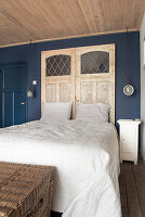 Old doors as a headboard in a bedroom with a blue wall