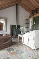 A sofa and an armchair in an open-plan living room in a former farmhouse