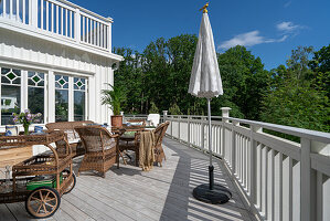 A sunny terrace with rattan furniture and a serving trolley