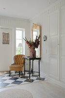 An upholstered chair, an antique table and a gold-framed mirror in a hallway