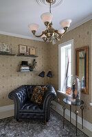 A leather armchair in the corner of a room with wallpaper