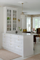 A white breakfast bar with a marble top and a display cabinet