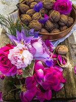 Arrangement of roses, crane's bill geraniums, clematis and walnuts