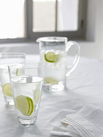 Carafe and glasses of water with lime slices in front of window