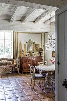Steintisch mit Stühlen im Essbereich mit Fliesenboden, im Hintergrund antike Kommode