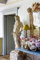 Console table with maritime decorations, mirror and statue next to doorway