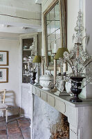 Fireside with chandelier, table lamp and candlestick, above mirror