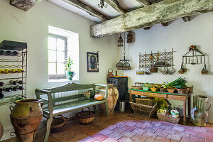 Shelves, amphorae, wooden bench and table in pantry