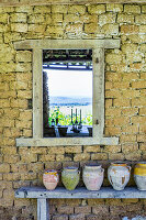 Wooden bench with clay pots in front of stone wall with window cut-out