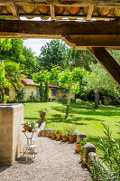 View from the veranda with wooden roof into the sunny garden