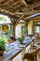 Long dining table with rattan chairs on the veranda with rustic wooden roof