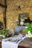 Covered dining table on the veranda of a stone house