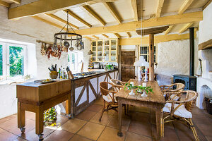 Wooden table with rattan chairs in country kitchen with wooden beamed ceiling