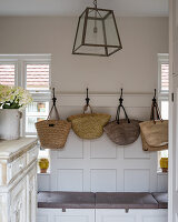 A selection of French wicker shopping baskets on iron coat hooks in boot room with pendant lamp