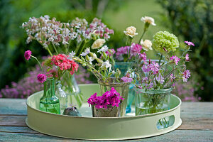 Small bouquets of carnations, light carnations, mustache and grass carnations on a round tray