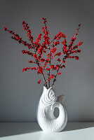 Branches of winterberry berries in fish-shaped vase