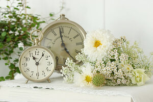 Vintage-style arrangement of cosmea, Queen Anne's lace, yarrow and snapdragons next to two clocks