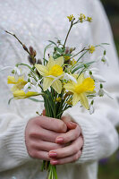 Woman holding bouquet of narcissus, snowdrops and cornelian cherry